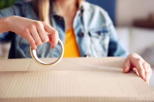 personne qui prépare boite déménagement_person preparing a box to move to a new house